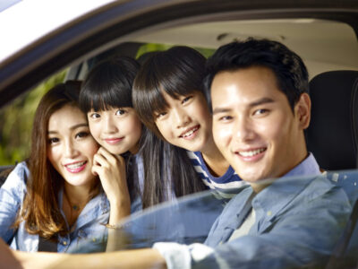 happy asian couple with their two children riding in car.