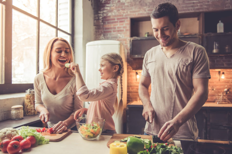 Cute little girl and her beautiful parents are cutting vegetables and smiling while cooking in kitchen at home