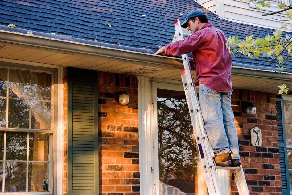 Man on Ladder Cleaning Gutter, Spring Home Maintenance, Checking Your Gutter System