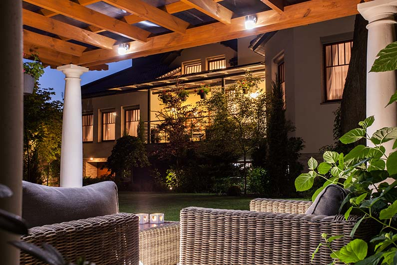 Backyard at night with pergola and furniture, outside garden