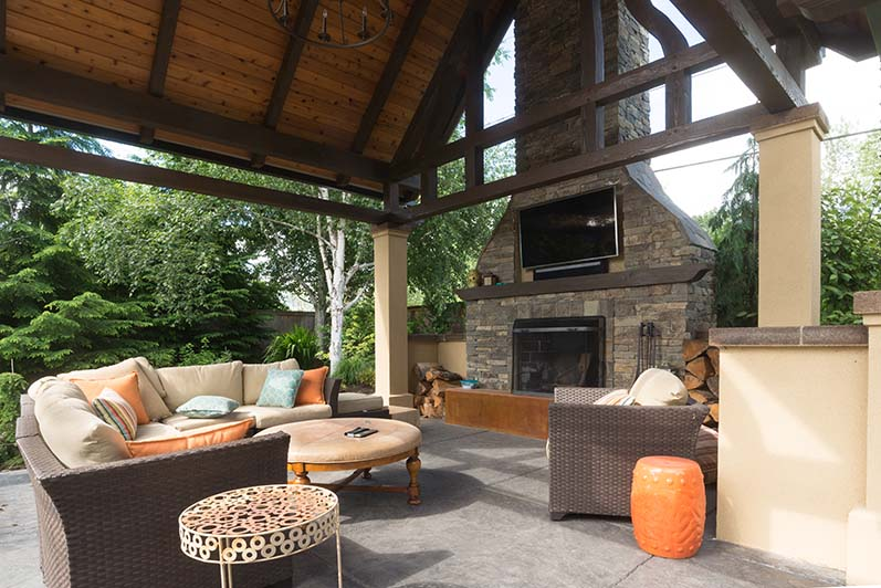 An upscale backyard terrace featuring perennials and with a custom designed shelter and fireplace.