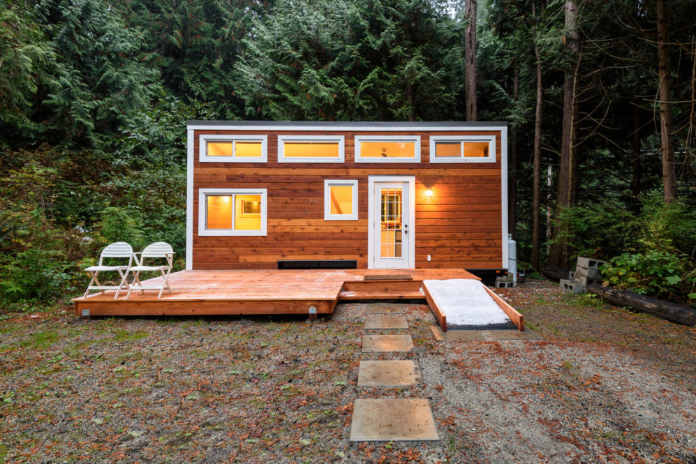 Tiny-house made of wood, set back in the trees with stone walkway.