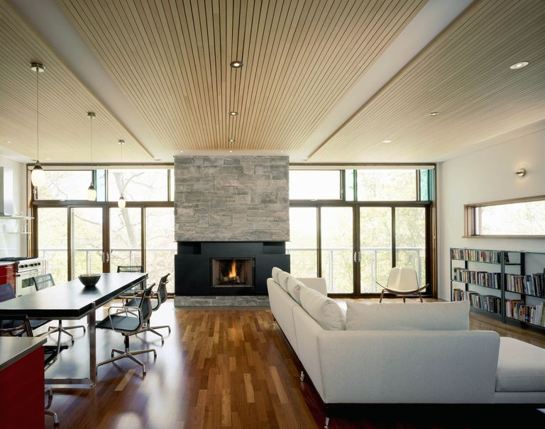 Living room and Kitchen interior with hard wood flooring, stone fireplace and row of windows