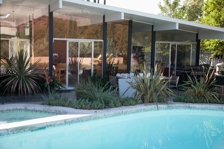 modern home with large glass windows and swimming pool