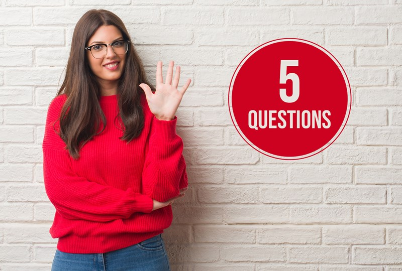 "Woma in red shirt against beige wall, with a red circle on the wall, text says, ""5 Questions""."