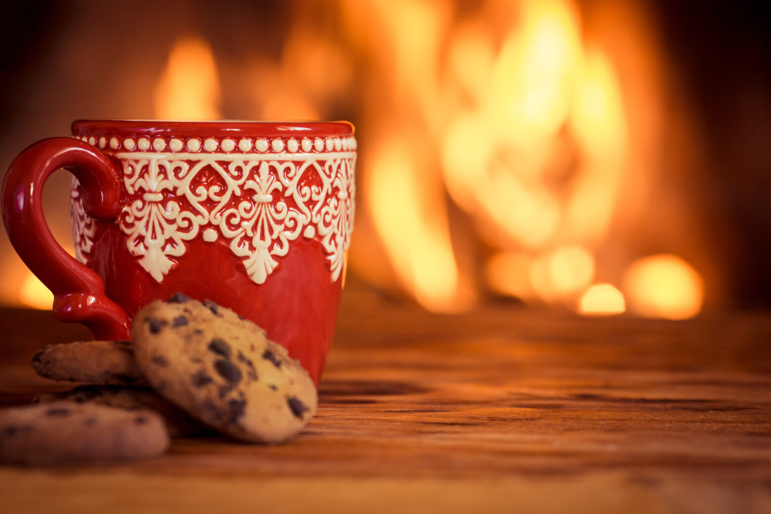 Red and white Christmas mug and chocolate chip cookie near the fireplace.
