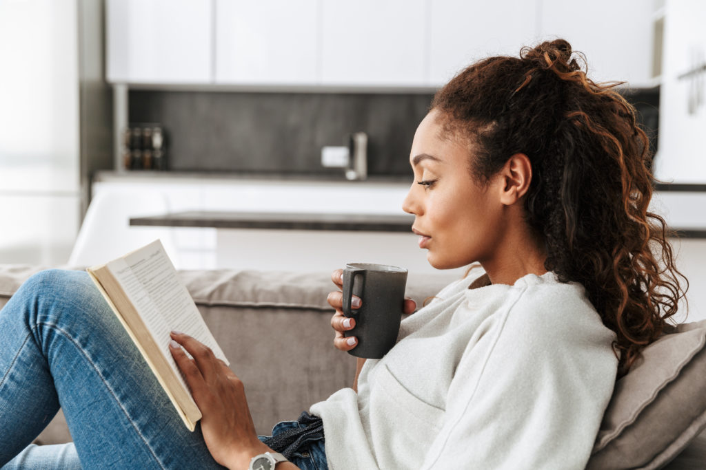 African American woman drinking tea and reading 7 Ways to Find Your First Home