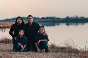 Family posing in front of lake